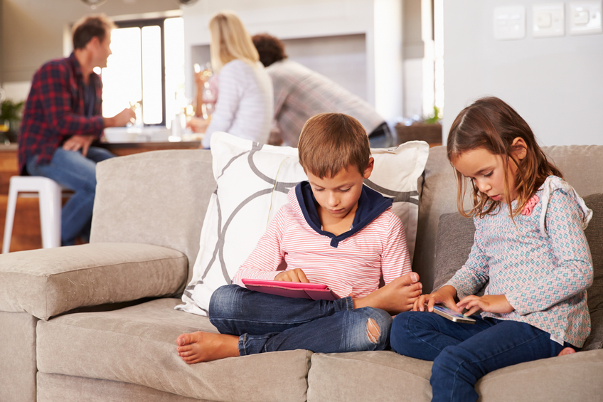 2 kids play on devices while their parents chat in the background
