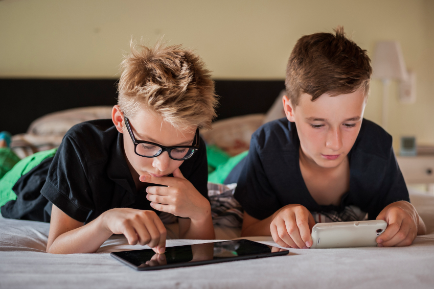 2 boys playing with their devices